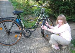 Ältere Frau putzt das Vorderrad ihres Fahrrades