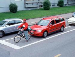 Älterer Radfahrer mit Helm wartet auf Kfz-Linksabbiegespur
