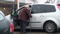 Eine ältere Frau mit Stock steigt auf der Fahrerseite in ein Auto ein.