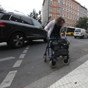 Auto biegt hinter einer Fußgängerin mit Rollator ab