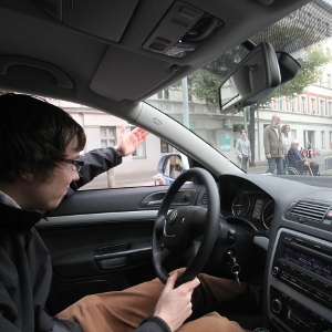 Ein Autofahrer gibt Fußgängern per Handzeichen Vorrang