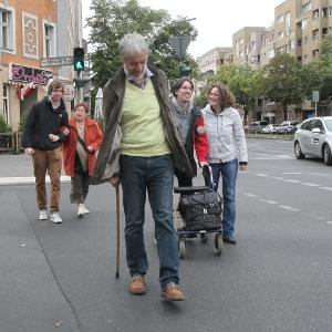 Fußgänger mit Gehhilfen queren die Fahrbahn